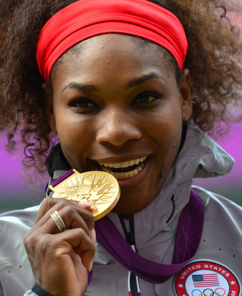 Serena Williams poses on the podium with her gold medal after defeating Russia's Maria Sharapova.