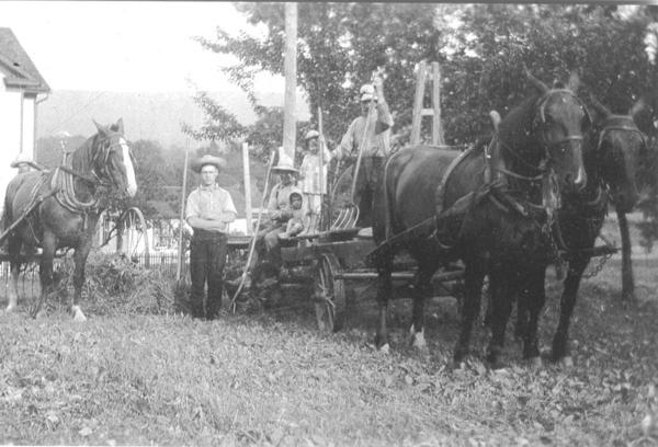 "Making hay with horse power in the 1930s  about a decade before the first Farmall H tractor made its debut on ""Blue Lick Valley Farm"" in Brothersvalley Township. Included in the picture is the author's father, Robert E. Hay, standing, and his Uncle John Engle barely visible behind the horse pulling the hay rake. On the hay wagon are Grandpa Nevin Hay, Aunt Romaine (Robinson), Cousin Francis Walker, and Uncle Edison Walker."