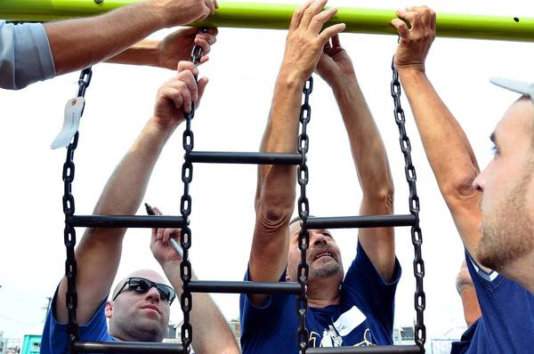 Local IronWorkers Union #36 President Brett Schaffer, left, of Allentown and Teamster Local 773 Joe Wieder, of Lower Macungie, work together with others to secure a chain ladder. Volunteers helped rebuild and beautify the Franklin Park Playground on Saturday.