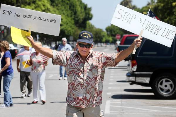 Korean War veteran Tom Bernacchi, 78, of Costa Mesa, shows his support for Costa Mesa Mayor Pro Tem Jim Righeimer as he walks from City Hall to the police station on Saturday.