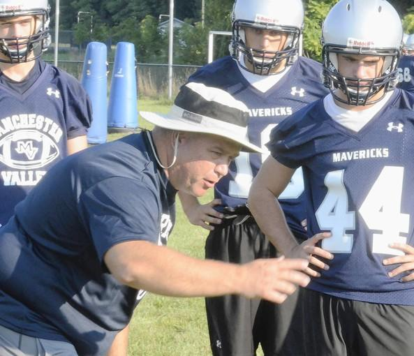 Manchester Valley head football coach Tony Sherman works with his backfield players during practice. The Mavericks are entering just their fourth season of existence, and hope to build on last year's .500 season.