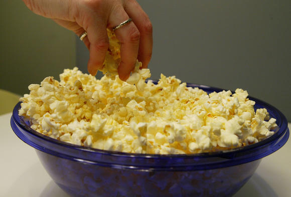 A woman grabs freshly popped microwave popcorn from a bowl