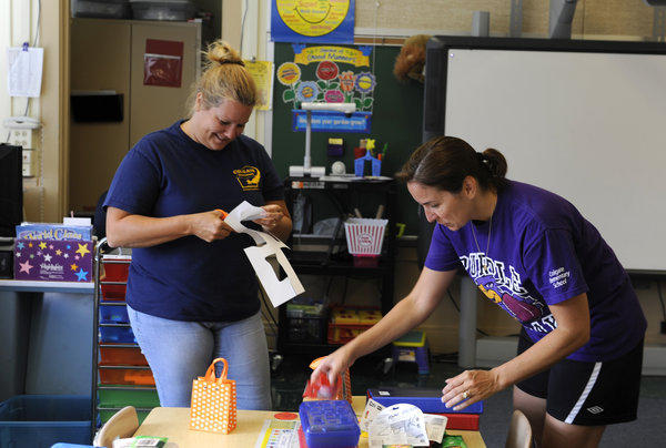 First grade teachers Rachelle Rasmussen, left, and Michele Baugher prepare Baugher's classroom at Colgate Elementary School for the first day of school.