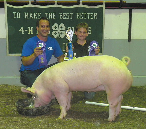 Isaiah Yoder of Chambersburg, Pa., right, exhibited the 2012 Franklin County grand champion 4-H market hog, which was purchased by YB Welding for $900, or $3.57 a pound. Representing YB Welding Inc. is Eric Yoder.