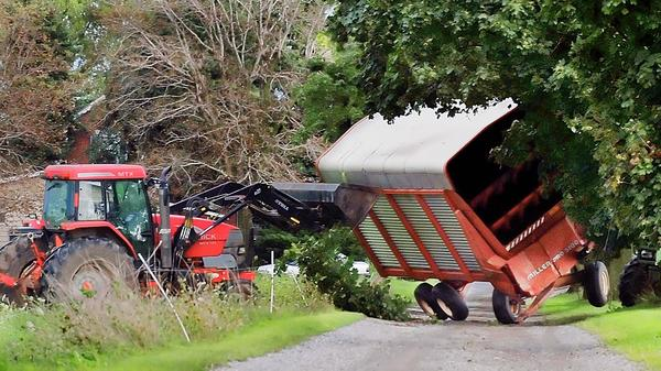 Phil Risser uses a tractor to upright a sileage wagon that was toppled Sunday at his farm on Williamsport Pike duirng a storm that came through Greencastle, Pa.