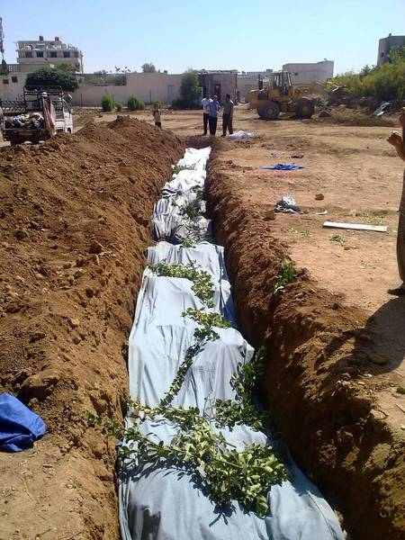 Covered bodies fill a mass grave reported to be in Dariya, Syria, where hundreds of people have been killed.