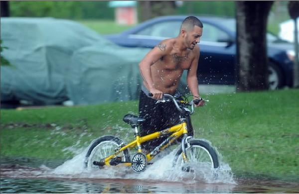 Jesus Rodriguez rides his bike through the flooded parking lot at Bent Tree West apartments off Boynton Beach Boulevard near Military Trail on Monday morning.