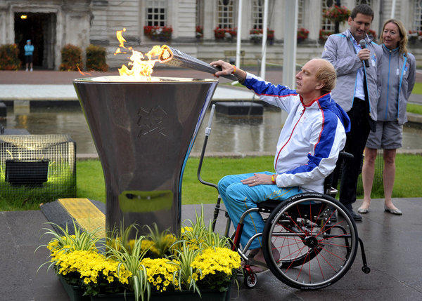 Torchbearer Simon Richardson lights the Paralympics caldron outside City Hall in Cardiff, Wales, on Monday.
