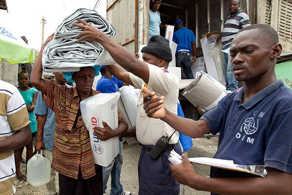 A resident receives aid from International Organization for Migration (IOM) in a camp for displaced people in Port-Au-Prince, August 26, 2012.