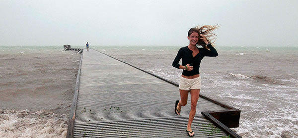 An unidentified woman leaves the pier in high wind and rough surf as Tropical Storm Isaac moves over the island August 26, 2012. Tropical Storm Isaac lashed south Florida with winds and heavy rain on Sunday after battering the Caribbean, disrupting plans for the Republican National Convention in Tampa and threatening to interrupt about half of U.S. offshore oil output.