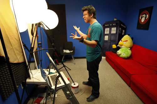 "Philip DeFranco delivers his lines to his camera during a run-through Aug. 21 in the simple studio of his Woodland Hills production offices where he records his show as host of the ""The Philip DeFranco Show,"" a news program on YouTube about news and pop culture. The show rivals Jon Stewart's ""The Daily Show"" in audience size. As the news anchor, DeFranco wears T-shirts instead of the standard-issue suit-and-tie, and the anchor desk has been replaced with a red futon decorated with stuffed characters."