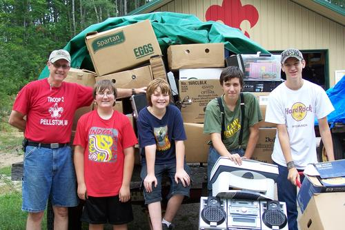 Pellston Boy Scout 2 assistant leader Gordon Graham(left) and scouts Jacob Czaplicki, Jacob Robbins, Joshua LeBlanc and non-member Josh Keber ready the many boxes of items for their annual garage sale.
