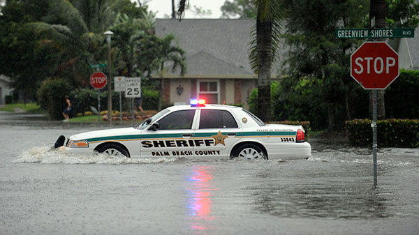 A Palm Beach County Sheriffs Deputy plows  through flood waters along Greenview Shores Blvd. in Wellington Monday morning after heavy rains from Tropical Storm Isaac inundated the area.