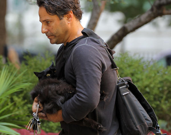 "Dan Kravitz carries his cat ""Puffy"" after Chicago Fire Department firefighters rescued and treated the cat while responding to a small blaze in a high-rise building."