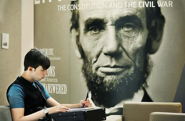 "Patrick Snouffer, a sophomore at Hagerstown Community College, takes notes Monday near the ""Lincoln, The Constitution and The Civil War"" exhibit at HCC's Kepler Center."