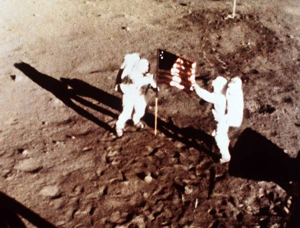 "Apollo 11 astronauts Neil Armstrong and Edwin E. ""Buzz"" Aldrin, the first men to land on the moon, plant the U.S. flag on the lunar surface."