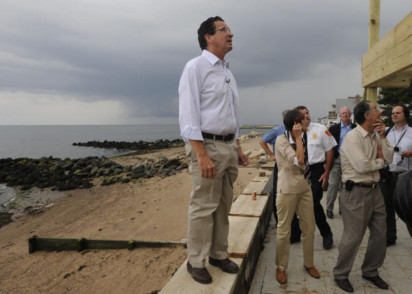 Gov. Dannel P. Malloy looks at a house under construction on Cosey Beach in East Haven Monday afternoon during  his tour of the area on the one year anniversary of Tropical Storm Irene.