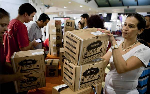 An Israeli woman collects her family's gas mask kits at a distribution center in a mall in Jerusalem last week.