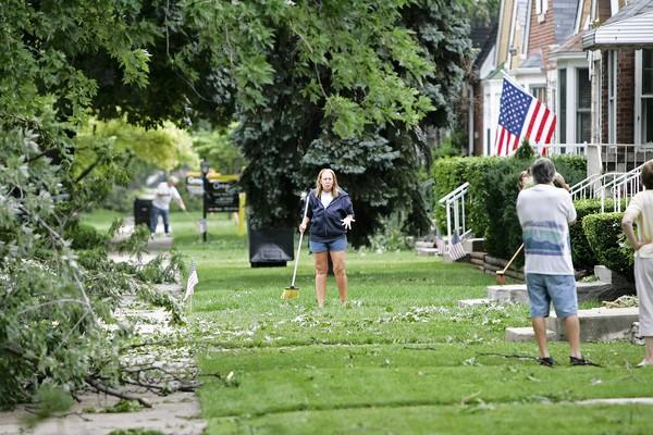 Bunny Otterson talks to neighbors as she sweeps up the sidewalk in front of her Jefferson Park home.