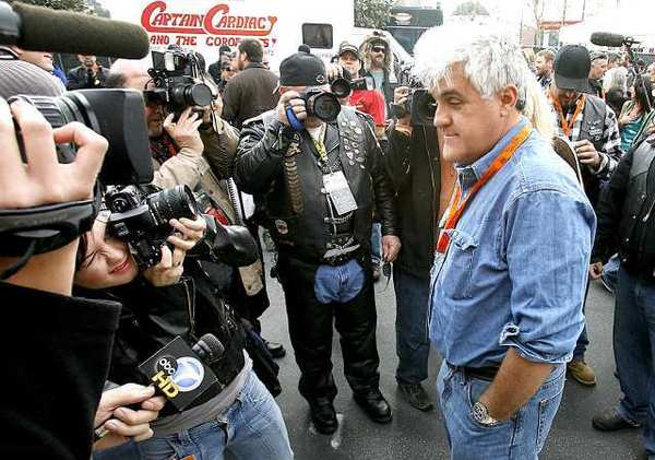 Jay Leno talks to news media and photographers.