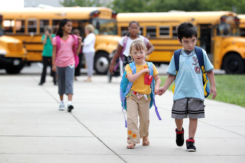Kindergarteners Maggie Kalis, left, 6, and Oswin Palma, 5, walk into school together on the first day at Hollifield Station Elementary School in Ellicott City.