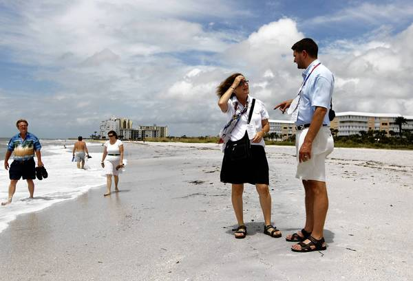 Kay Ferris, a GOP delegate from Sterling, Ill., and Andy Blankenbaker, an alternate delegate from Galena, wander St. Pete Beach, Fla., on Monday. Tropical Storm Isaac delayed the start of the Republican National Convention's activities at the Tampa Bay Times Forum until Tuesday.