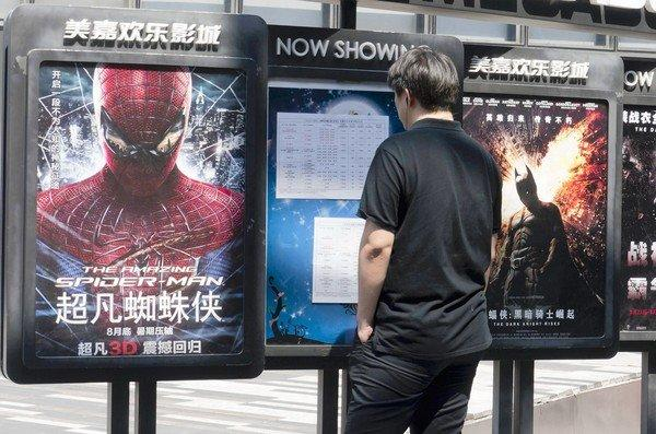 "Hollywood blockbuster movies ""The Amazing Spider-Man"" and ""The Dark Knight Rises"" are advertised as coming at the end of August in central Beijing."