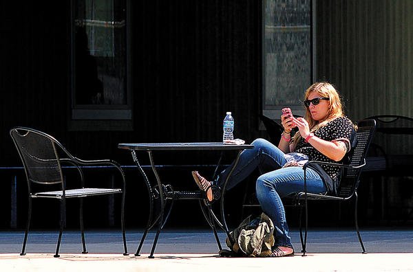 Kristi Geist finds a sunny location between classes at Shepherd University Monday to check her cellphone. Geist transferred from Northern Virginia Community College and will study art education.