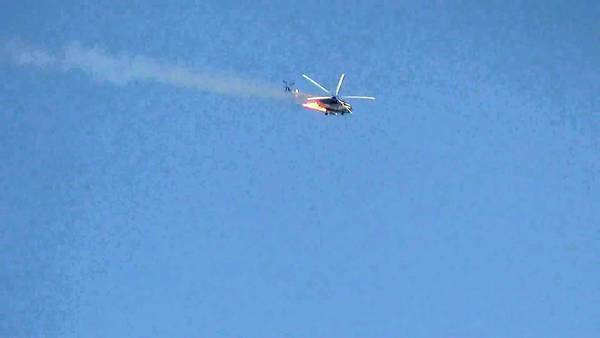 A burning Syrian combat helicopter goes down over Damascus in an image from video on YouTube.
