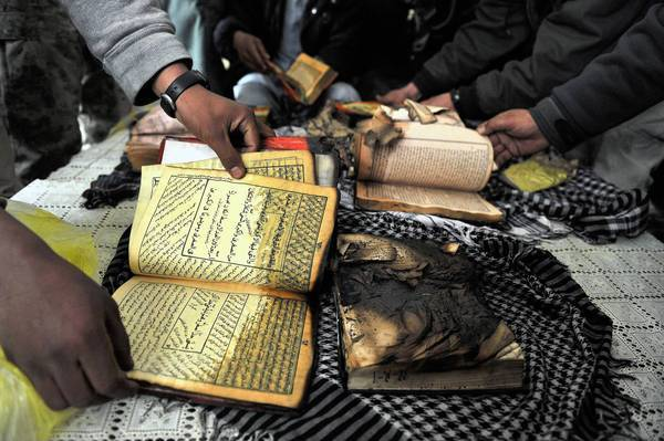 A demonstrator shows a damaged Koran during a protest in February at the gate of Bagram air base north of Kabul in Afghanistan.