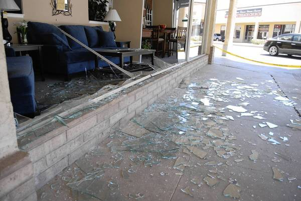 Broken glass covers the sidewalk in front of a Brawley furniture store after an earthquake Sunday.