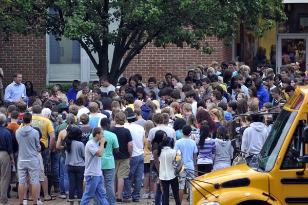 People gather to pray outside Perry Hall High School as students return for the second day of classes.