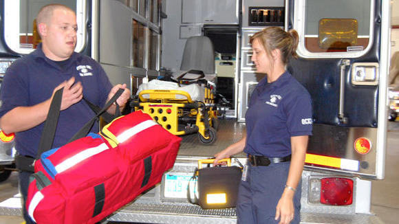 "Otsego County EMS Rescue staff member Brandon Pendry grabs the ""jump bag"" with emergency supplies while Amanda Viviano grabs the bag with the defibrillator used for life-threatening heart situations."