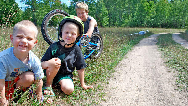 Thor Krantz, 4, Axel Krantz, 5, and Brady Dexter, 11, (l-r) fix their bike on a two-track road near their neighborhood. A family dog was hit and killed by a truck near this spot last week, and the accident is a stern reminder that motorists and pedestrians should watch out for each other on local two-track roads.