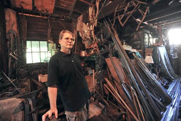 Tom Turtzo, a blacksmith from Plainfield Township, stands in his workshop on Tuesday.