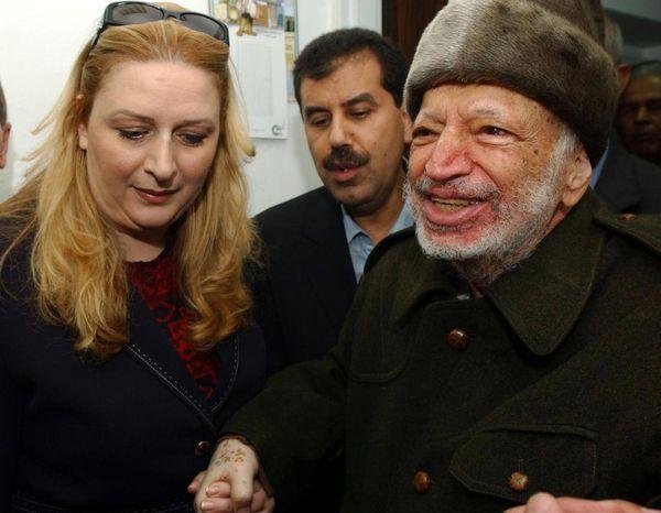 Yasser Arafat, right, assisted by his wife Souha, leaves his West Bank headquarters in Ramallah in October 2004, shortly before his death.