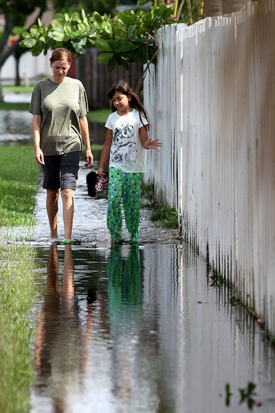 Tina Hansen and her daughter, Isabel Nanhoe, 8, inspect their flooding surrounding their home in Lauderhill Tuesday, August 28, 2012. The streets south of Commercial between NW 82 Ave and Pine Island Road remained flooded Tuesday after Tropical Isaac was clear of Florida.