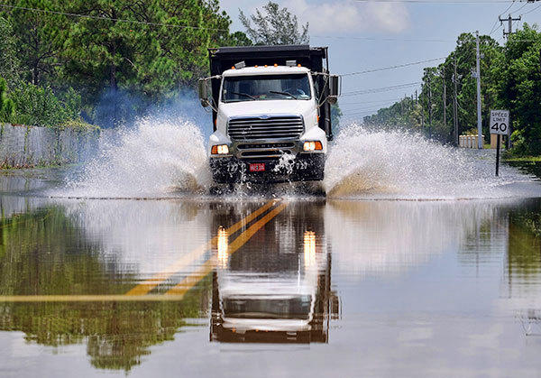 A dump truck plows through flood waters covering Tangerine  Blvd. in The Acreage   Tuesday afternoon.  Much of the area was inundated by heavy rains from Tropical Storm Isaac.