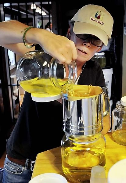 Bloomery Plantation Distillery co-owner Linda Losey pours 190-proof, lemon-infused alcohol through filters during the process of preparing limoncello, a sweet, lemony liqueur originally developed in Italy.