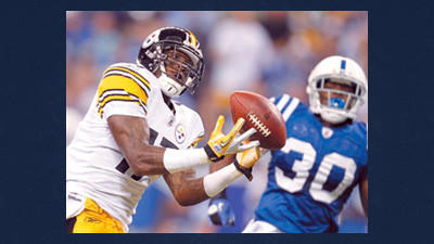 This Sept. 25, 2011 file photo shows Pittsburgh Steelers wide receiver Mike Wallace (17) making a touchdown reception in front of Indianapolis Colts defensive back David Caldwell (30) during the first quarter of an NFL football game in Indianapolis. With less than two weeks before the start of the regular season, Pro Bowl receiver Wallace reported to the Steelers on Tuesday.