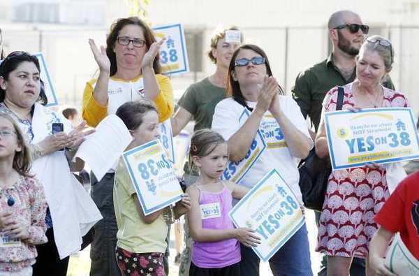 Attendees applaud in support of the comments made at Olive Park in Burbank where PTA members, local teachers, parents and community leaders rallied Tuesday for Proposition 38 which would guarantee $77 million for Burbank schools for the next 12 years.