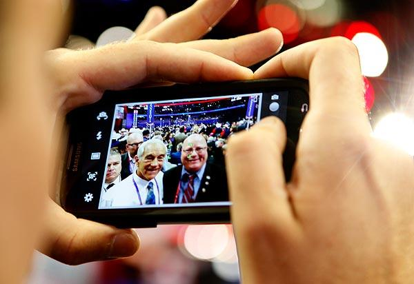 A supporter gets a picture with Rep. Ron Paul of Texas, left.