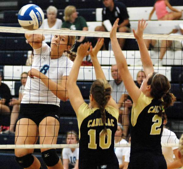 Petoskey senior middle hitter Megan Tompkins (left) spikes the ball as Cadillac senior Lexi Oddy (10) and junior Morgan Kelley (2) attempt the block during Tuesday's Big North Conference match at the Petoskey High School gym. The Northmen fell to the Vikings in five sets.