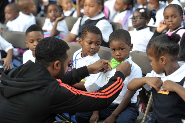 Nathaniel Tyler, Jr., straightens his son's bowtie. Norian Tyler, 4, is sitting with his Leith Walk Elementary pre-k classmates on the first day of the school year. Baltimore city officials, joined by state and local political and education leaders, kick off the first day of school at Leith Walk Elementary, which will welcome students to a brand new $32 million, state-of-the-art building this year.