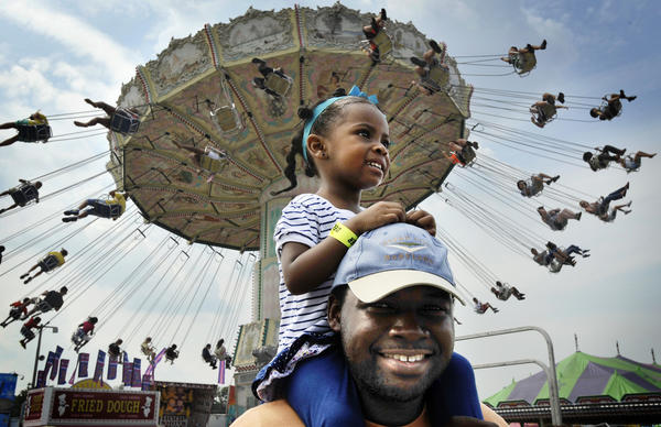 Noah Rayner (CQ) and his daughter, Naomi Rayner,2, of Baltimore enjoy the day at the Maryland State Fair with the Giant Swing behind them. Maryland State Fair in Timonium opens for first day.