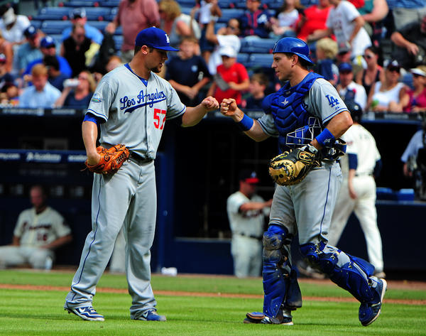 Scott Elbert, left, and A.J. Ellis celebrate a victory over the Atlanta Braves on Aug. 19.