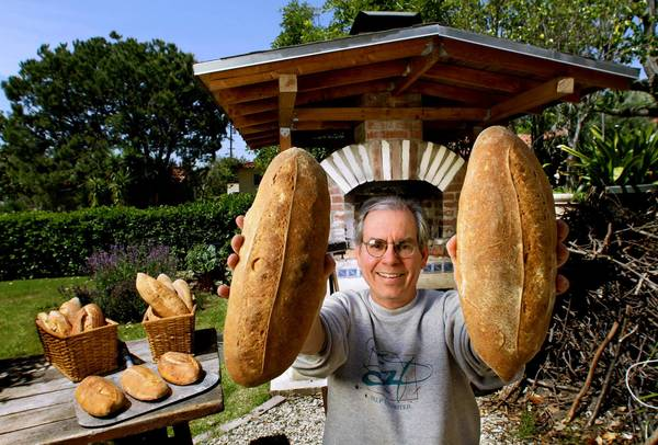 Mark Stambler shows a couple of loaves of bread he baked in his backyard wood-burning oven. He had been selling about 50 loaves a week until the Los Angeles County Health Department ordered him to stop.