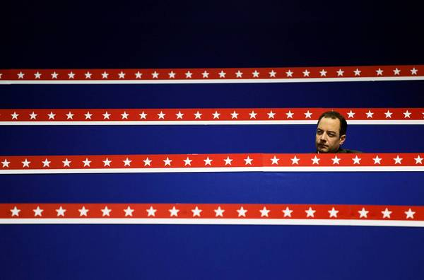 RNC Chairman Reince Priebus sits at a desk before the start of the third day of the Republican National Convention.