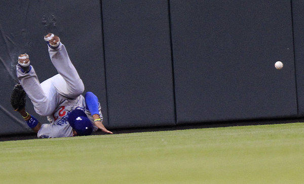 Matt Kemp falls to the ground after crashing into the wall.