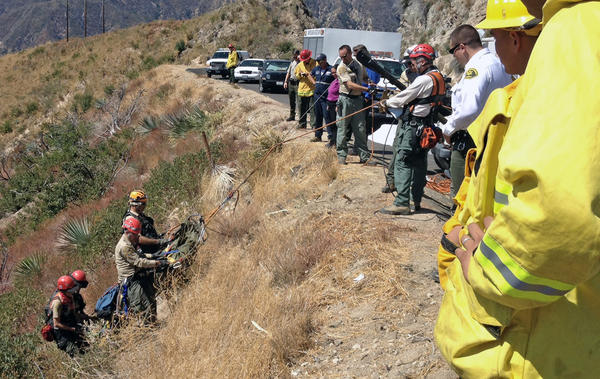 Emergency crews recover the body of a man who died when his car plunged off the Angeles Crest Highway Wednesday, Aug. 29.